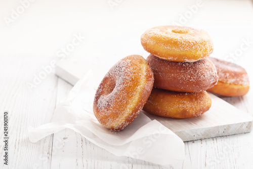 Photo Donuts on white wooden table. Copy space