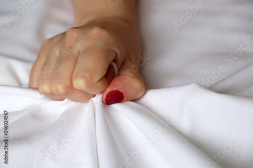 Wallpaper Mural Female hand with red nails pulling and gripping white bedsheet in ecstasy