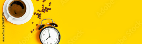 Obraz na plátne Flat lay cup of black coffee, coffee beans, black alarm clock on yellow background top view copy space