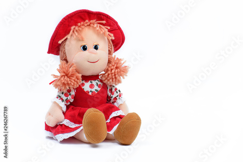 Photo Soft doll in a red dress and hat on a white background