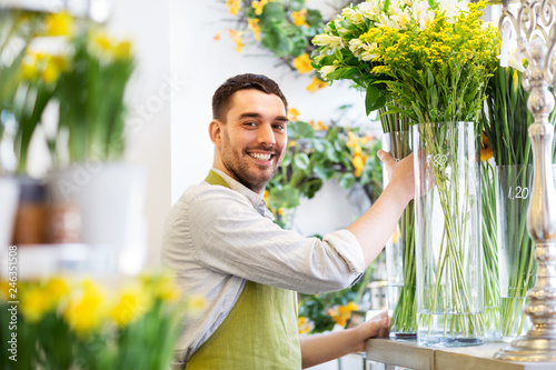 small business, sale and floristry concept - happy florist man setting flowers at flower shop
