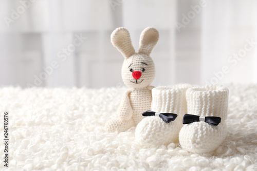 Handmade baby booties and stuffed rabbit on plaid against blurred background. Space for text