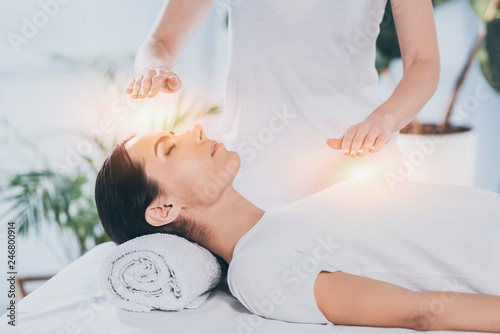 Cuadros en Lienzo side view of calm young woman receiving reiki healing therapy on head and chest