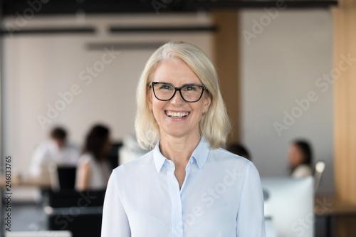 Obraz na płótnie Cheerful senior businesswoman in glasses looking at camera, happy older team lea