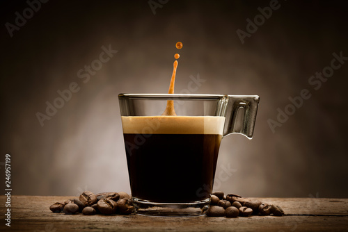 Fotografia Black coffee in glass cup with coffee beans and jumping drop, on wooden table