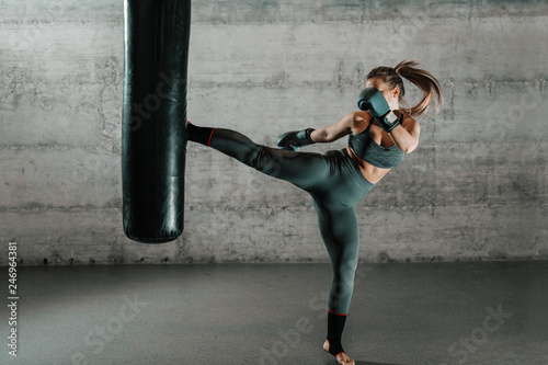 Photo Caucasian woman in sportswear and with boxing gloves kicking bag in the gym