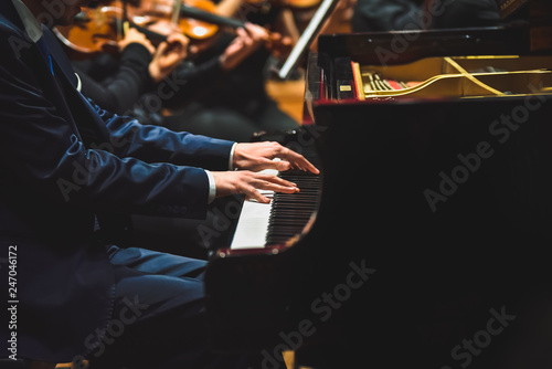 Fototapeta Pianist playing a piece on a grand piano at a concert, seen from the side