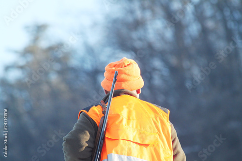 Hunter with high visibility clothing and rifle, waiting for boar hunting in snowy countryside Poster Mural XXL