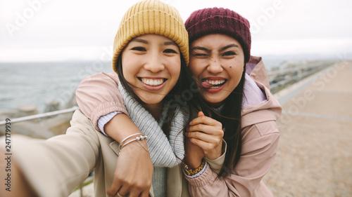Cheerful women friends having fun standing outdoors