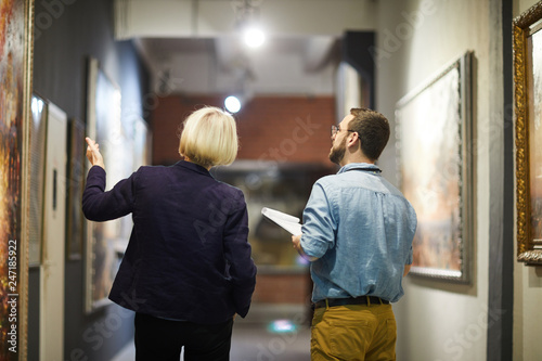 Fotografia Back view portrait of two museum workers discussing paintings walking in art gal