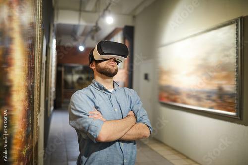 Valokuva Waist up portrait of modern man wearing VR headset during virtual tour in art ga