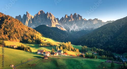 Landscape with village with houses, church, green meadows, trees, rocks, blue sky. Santa Maddalena in mountain valley at sunset in autumn in Dolomites, Italy. St. Magdalena and mountains. Val di Funes