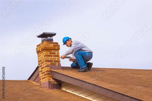 Billede på lærred Contractor Builder with blue hardhat on the roof caulking chimney