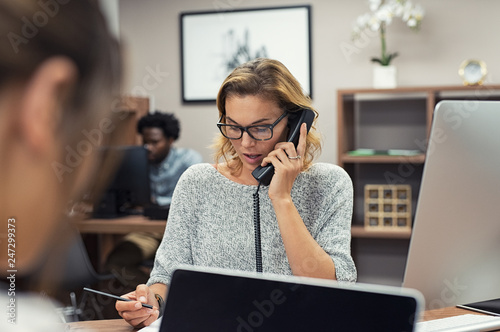 Foto Businesswoman talking on phone at office