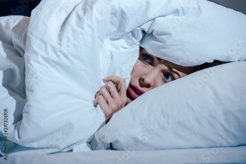 Fotografia scared woman hiding behind blanket in bedroom at home