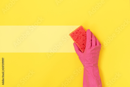 Woman holding sponge for washing in her hands against yellow background