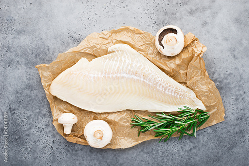 Wallpaper Mural Fillet of sea white cod fish on parchment with fresh raw champignons before cooking