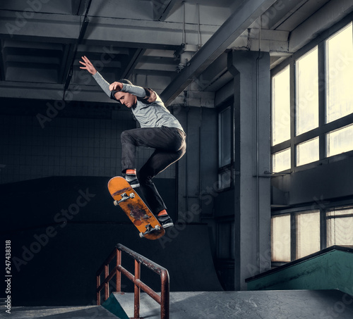 Obraz na plátně Skateboarder performing a trick on mini ramp at skate park indoor