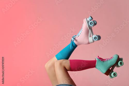 Obraz na płótnie Woman with vintage roller skates on color background, closeup