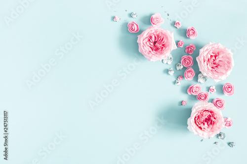 Fototapeta premium Kompozycja kwiatów. Rama wykonana z kwiatów róży na pastelowym niebieskim tle. Walentynki, dzień matki, dzień kobiet, koncepcja wiosna. Leżał płasko, widok z góry, miejsce kopiowania