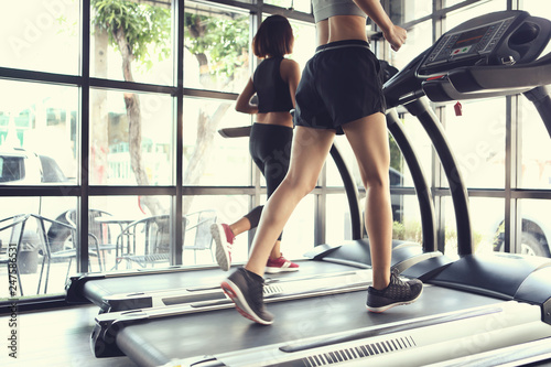 The legs of two young women running on an electric treadmill for exercise Fototapeta
