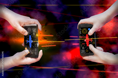 Fototapeta Two pairs of hands hold smartphones and enthusiastically play mobile online game