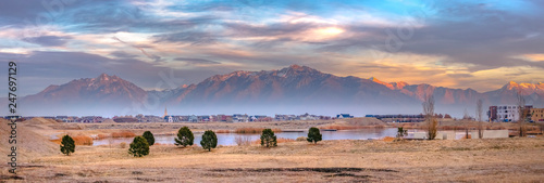 Fotografia Lake and homes against sunlit mountain in Daybreak