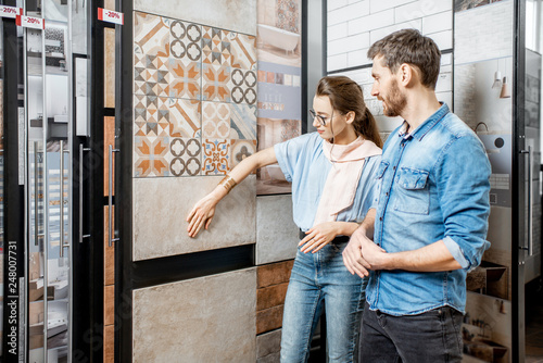 Stampa su Tela Beautiful young couple choosing ceramic tiles for their house repairment in the