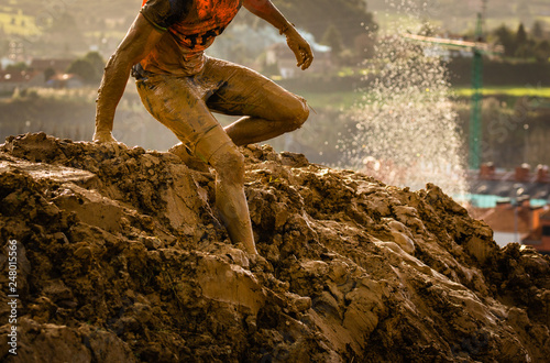 Obraz na plátne Trail running athlete crossing the dirty puddle in a mud racer.