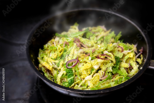 Fototapeta cooking green savoy cabbage with red onions in a black pan on a stove, healthy w