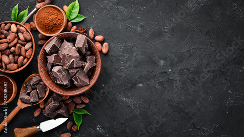 Cocoa beans, chocolate, cocoa butter and cocoa powder on a black background. Top view. Free copy space.