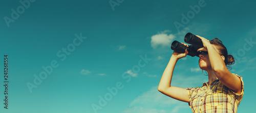 Foto Beautiful Young Girl Looking Through Binoculars On Blue Sky Background