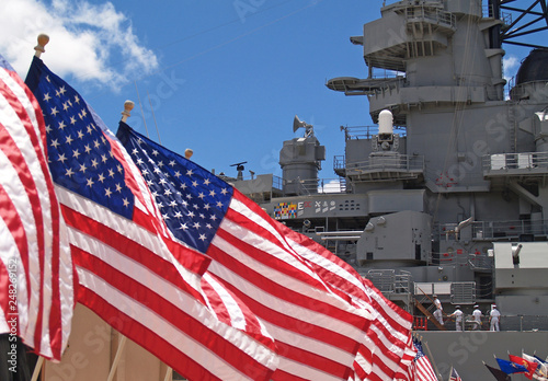Stampa su Tela US flags flying beside the Battleship Missouri in Pearl Harbor, Honolulu, Oahu, Hawaii with 4 sailors walking on deck