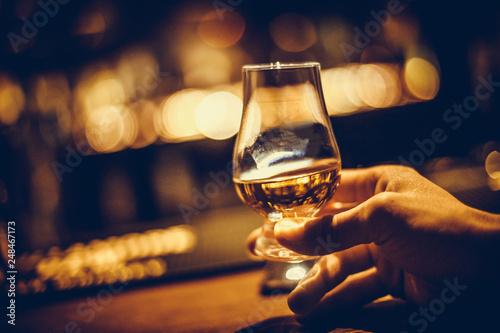 Fototapeta Hand holding a Glencairn single malt whisky glass