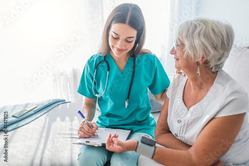 Fototapeta Nurse measuring blood pressure of senior woman at home