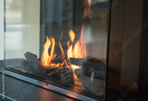 Carta da parati a fire burns in a glass fireplace, radiates heat