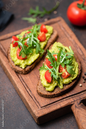Canvas Print Healthy toast with avocado, tomato, arugula on a wooden serving board