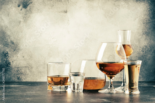 Fotografia Selection of hard strong alcoholic drinks in big glasses and small shot glass in assortent: vodka, cognac, tequila, brandy and whiskey, grappa, liqueur, vermouth, tincture, rum