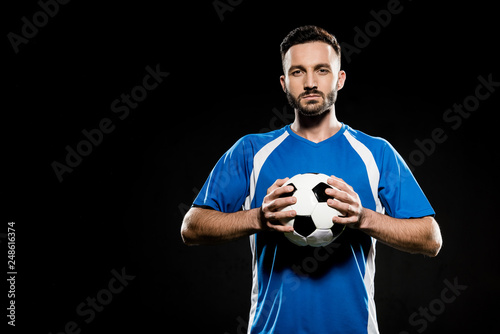 Stampa su Tela football player holding ball in hands isolated on black