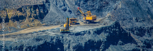 Canvas Print loading of mined iron ore in a pit to excavators in a cargo diesel dump truck