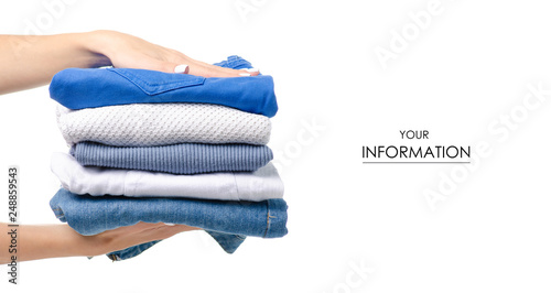 Obraz na plátně Stack of clothing jeans sweaters in hand pattern on a white background isolation