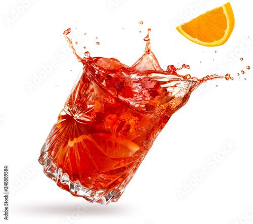 orange slice falling into a splashing negroni tilted on white background