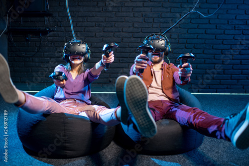 Man and woman shooting with gamepads while playing in virtual reality using VR h Fototapeta