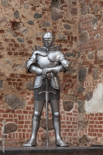 Tela Knight in full armor with a sword against the background of the ancient walls of
