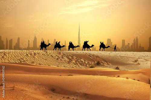 Canvas Print Camel caravan on sand dunes on Arabian desert with Dubai skyline at sunset