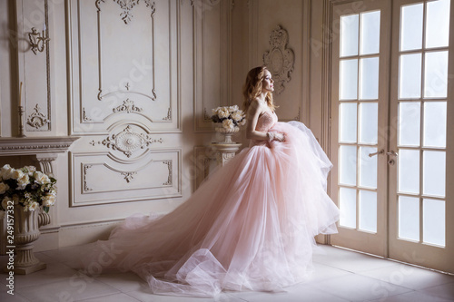 Fotografia Beautiful young blond woman in luxurious long pink dress posing in vintage room interior