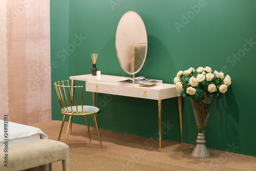 Valokuva White dressing table with wicker elements, a room with a green wall and golden b