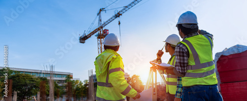 Fotografiet Construction engineers discussion with architects at construction site or building site of highrise building with Surveying for making contour plans is a graphical representation of the lay in land