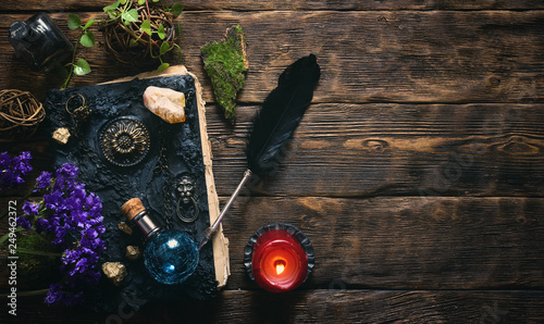 Photo Spell book, magic potions and other various witchcraft accessories on the wizard table background with copy space