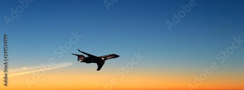 Fotografia business jet airplane flying on beautiful sunset sky landscape background at dus
